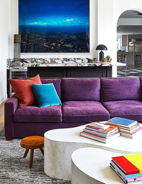room with large tv on wall and purple sofa at center