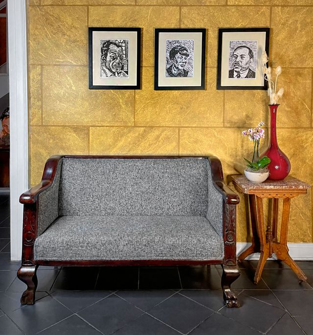 interior showing clawfoot gray settee against gold toned walls with artwork