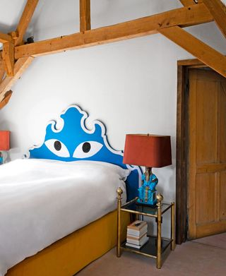 bed with headboard that has eyes drawn on it