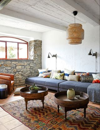 living room with blue sofa, stone wall, and large red rug