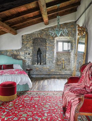 bedroom with standup gilded mirror, large red rug and stone walls