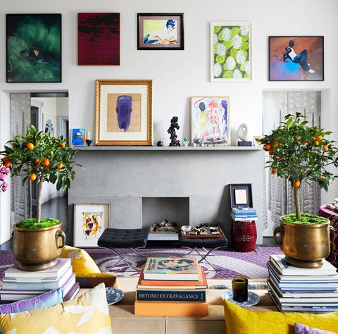 living room with small potted orange plants and fireplace with art