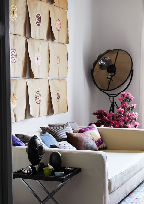 suede sofa with artwork above and small dark side table