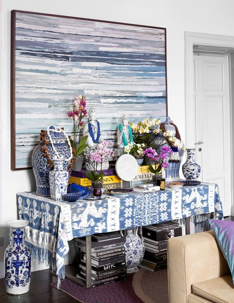 console draped with blue ikat and blue and white porcelain vases and books