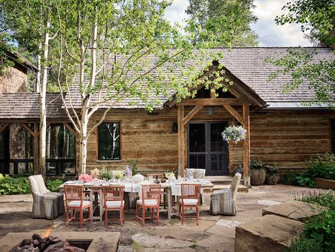 jeffrey bilhuber dining chairs on a stone patio in front of a rustic log house