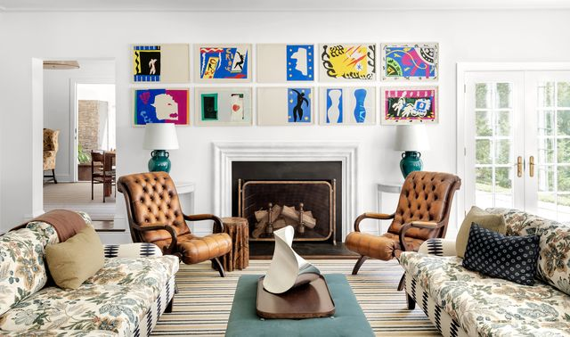james huniford white living room with artwork over the mantel and brown leather chairs