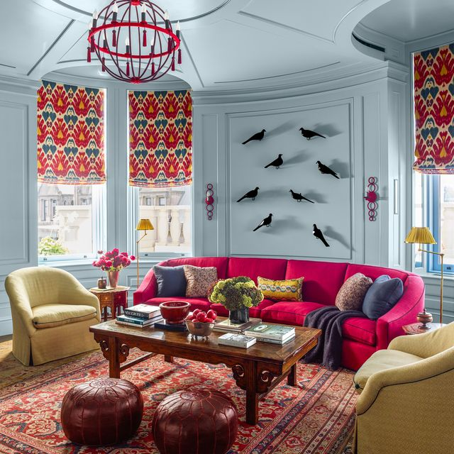 katie ridder living room with red sofa and yellow chairs and two leather poufs