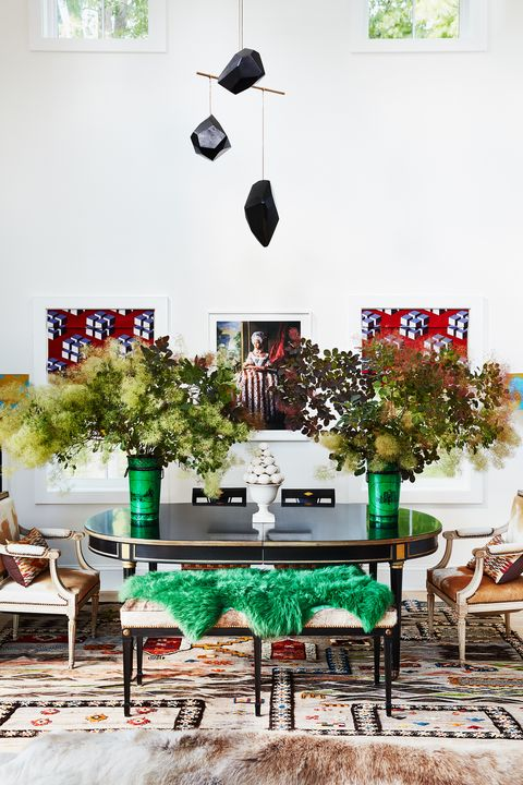 center dining table with large vases with flowers in a high ceiling room with an art mobile hanging from above