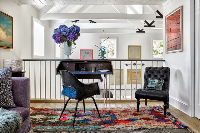 landing with small table, rug, and chairs overlooking room with art on walls