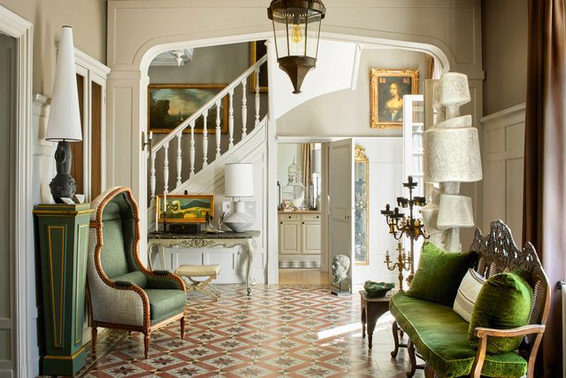 entryway of the manor with green chair and green sofa
