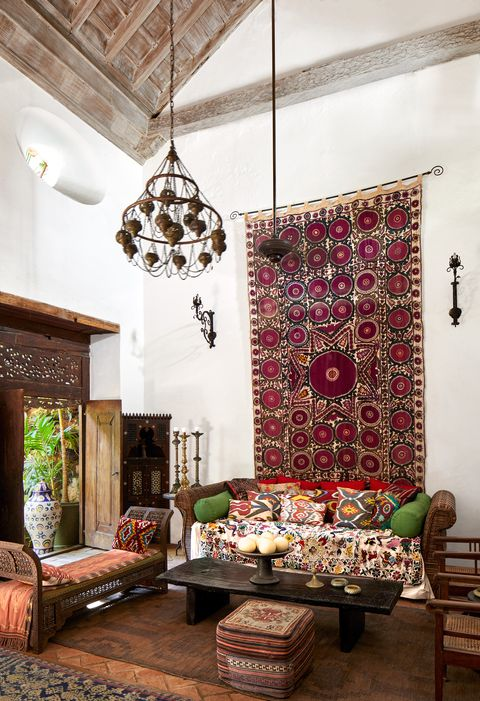 living area with  moroccan bench, a turkish pouf, and sconces and a large drapery hanging behind sofa on wall