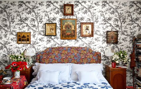 bed with upholstered headboard against a patterened wall