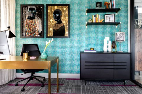 office with light blue tiled walls and two gold fleck pieces of art hanging over the desk