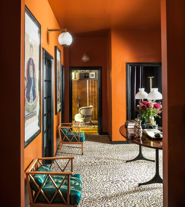 orange living room with rattan chairs and leopard pattern carpet and art on walls