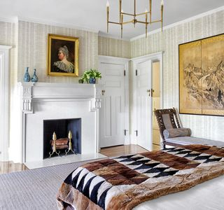 bedroom with fireplace, white walls, painting, and bed with brown and black patterned throw