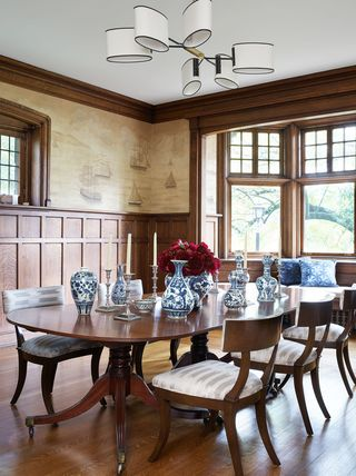 dining room with wood table, wainscoting and doors open to outside