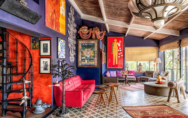 living room with purple walls and red sofas and accents of wood