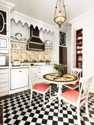 kitchen with black and white checked floor, small table, floral backsplash