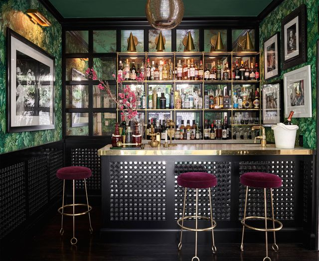bar with  leafy wallpaper and jean royère barstools
