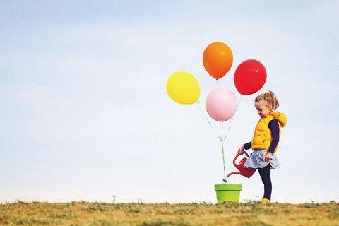 Cute blonde little girl is seeding and watering colorful balloons