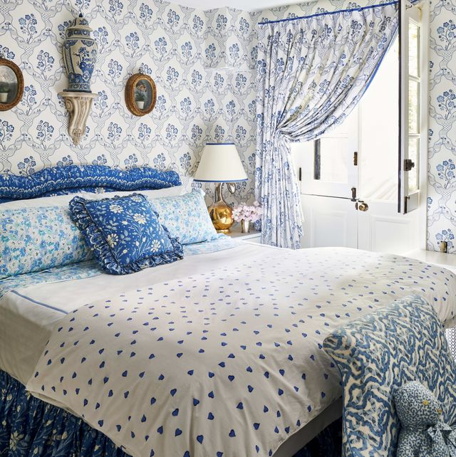 a blue and white bedroom with a custom headboard  and bed skirt  with lots of pattern