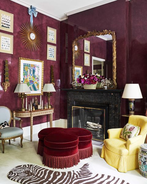 a 19th century french sunburst clock is suspended by a shantung silk bow from mario buattas living room and a velvet ottoman is on the floor in the aubergine walled room