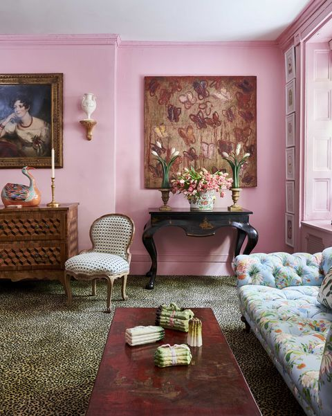 pink walls and leopard print carpet in a room with a floral tufted sofa