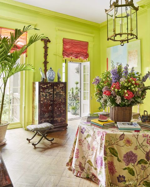 the upper salon is lime green with an octagonal table in the middle skirted in a floral tablecloth