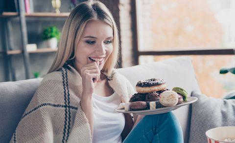 Vrouw met bord vol donuts en lekkernijen