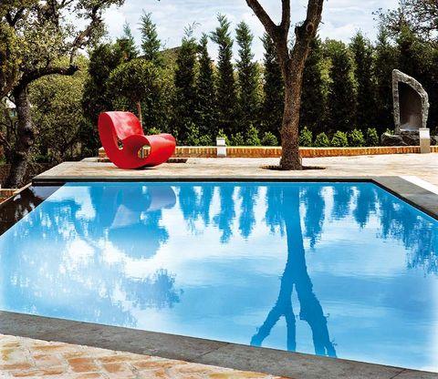 piscina en cascada con butaca roja