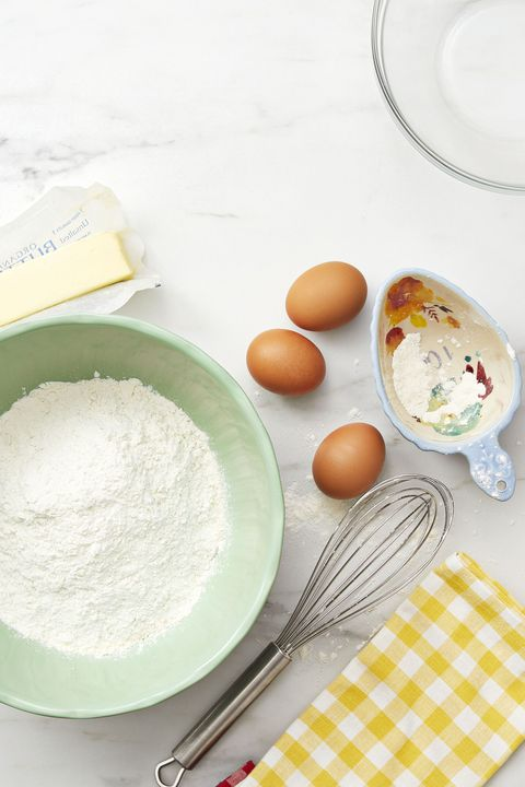 baking ingredients on kitchen counter   flour, butter, eggs, whisk