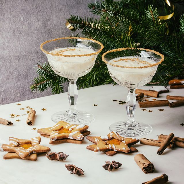 eggnog christmas milk cocktail, served in two vintage crystal glasses with shortbread star shape sugar cookies, cinnamon sticks, fir branch over white marble table