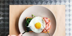 Eating breakfast with Belgian waffle, bacon, spinach and fried egg, personal perspective view