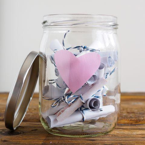 einmachglas mit rosa herz und zusammengerollten notizzetteln