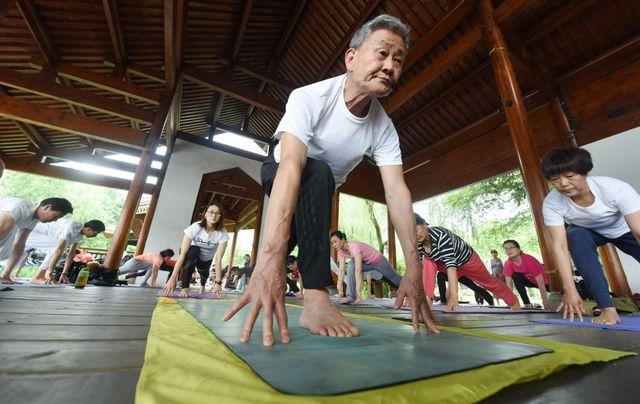 un anciano hace yoga en china