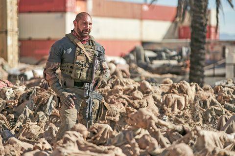 dave bautista, caracterizado con atuendo militar y metralleta en la mano, está entre  esqueletos humanos amontonados en una escena de la película ejército de los muertos, de zack snyder