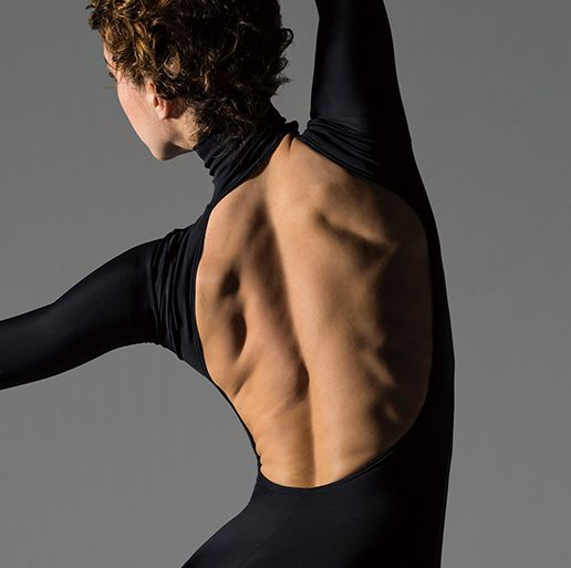 ballet dancer in pointe shoes and leotard performing piqué on pointe with the back to the audience