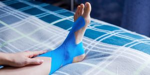 Elastic therapeutic blue tape applied to patient's left leg.