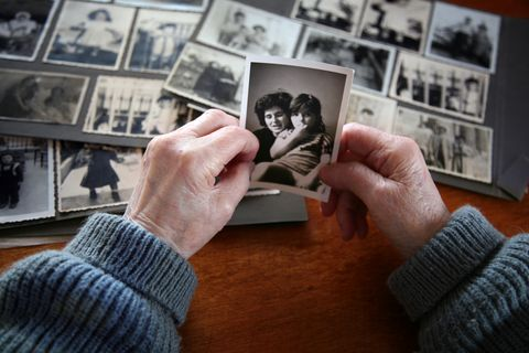 Elderly hands looking at old photos of self and family