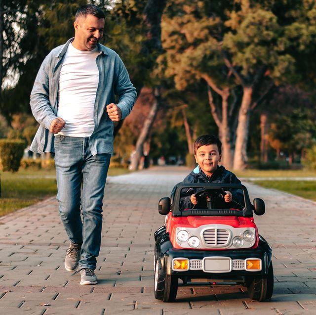 dad running alongside kid riding electric car