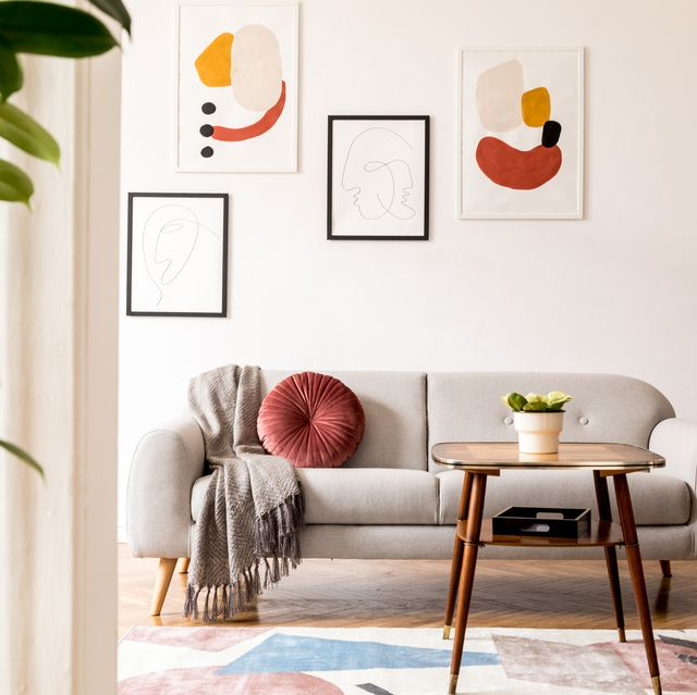 elegant and vintage apartment interior with classic wooden furniture, grey sofa, retro coffee table, lamp and mock up posters gallery brwon parquet, stylish carpet and plants bright space