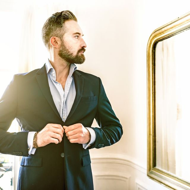 elegant bearded businessman dressing suit in front of mirror