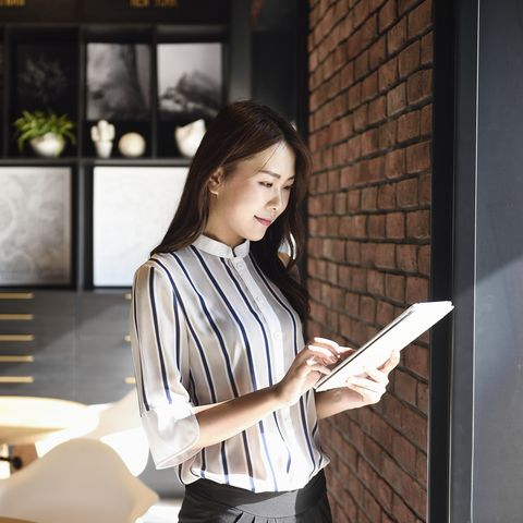 elegant chinese business woman using a tablet in an office