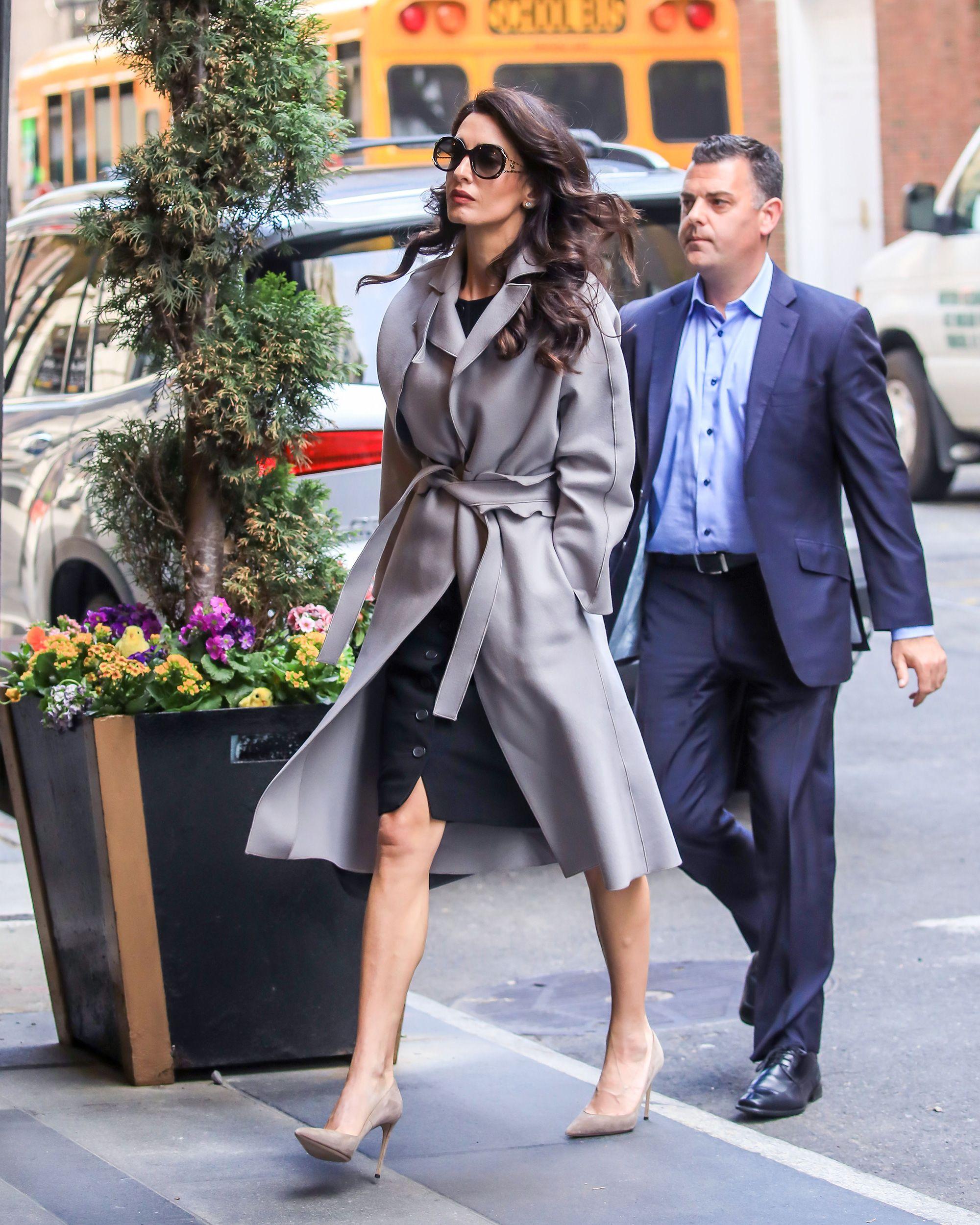 Amal Clooney sabe que el look 'working' de entretiempo perfecto para un día de lluvia mezcla gabardina y vestido negro