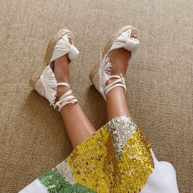 plano medio de los pies de una chica que lleva unas alpargatas con cintas de color blanco