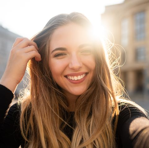 Self portrait of playful smiling young woman