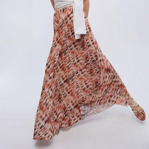modelo posando con una falda larga en tonos coral, una camisa blanca anudada y sandalias