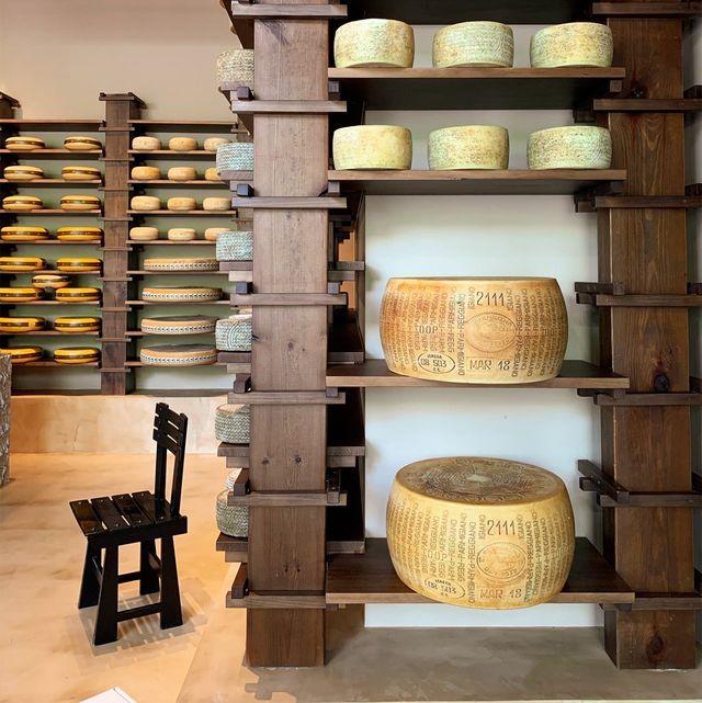 tienda de quesos con estanterías llenas de quesos gigantes