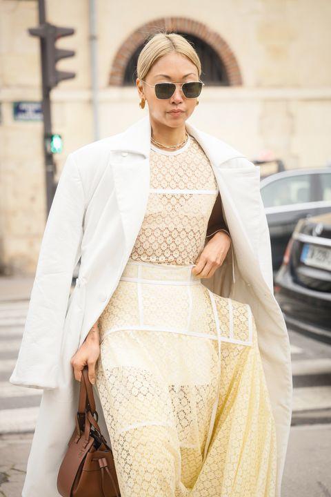 Inspiración street style con vestido de encaje amarillo suave y abrigo blanco