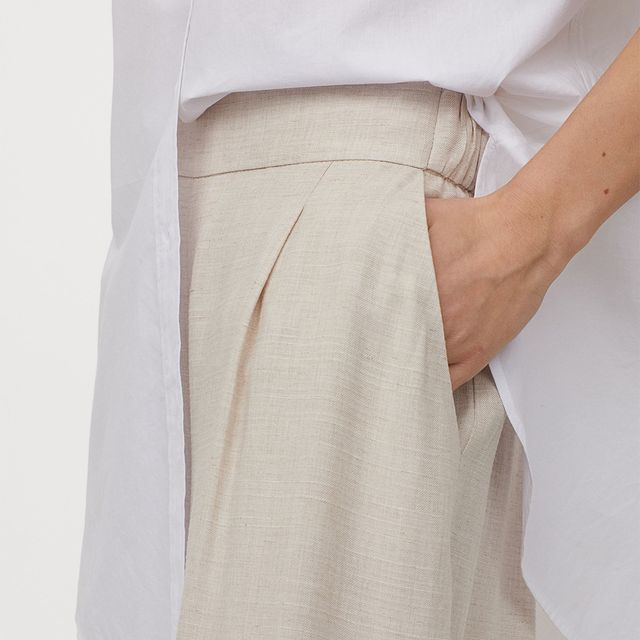 modelo posando con pantalon beige y camisa blanca